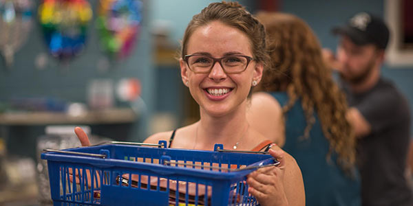 Student smiling while holding a basket full of items from the Campus Store