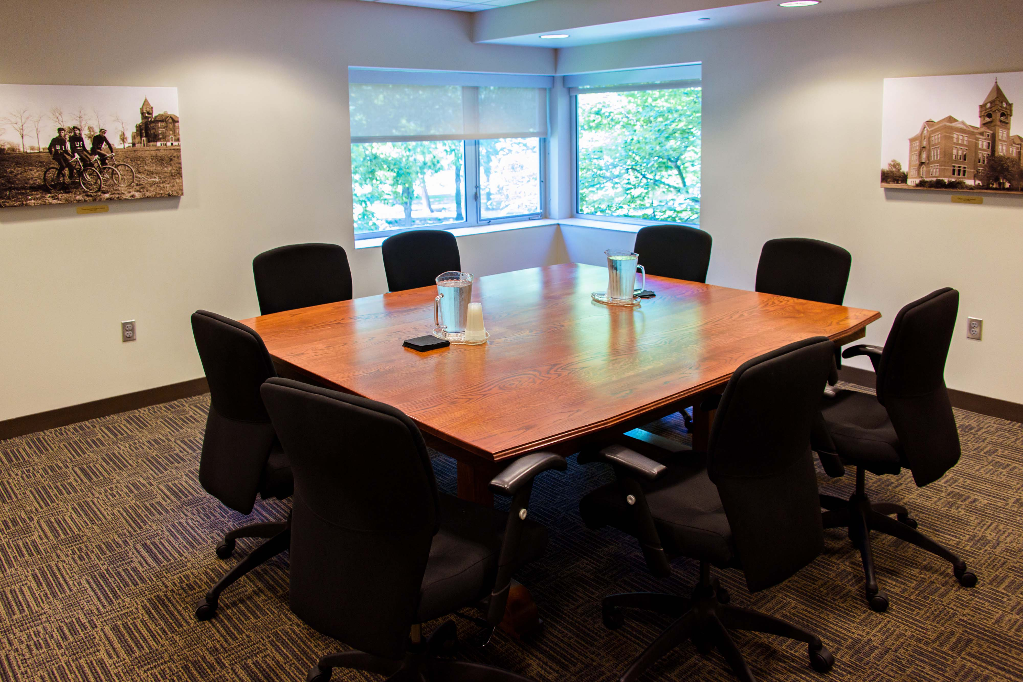 A view of the Bollinger Conference Room that shows its corner window, table, and seating