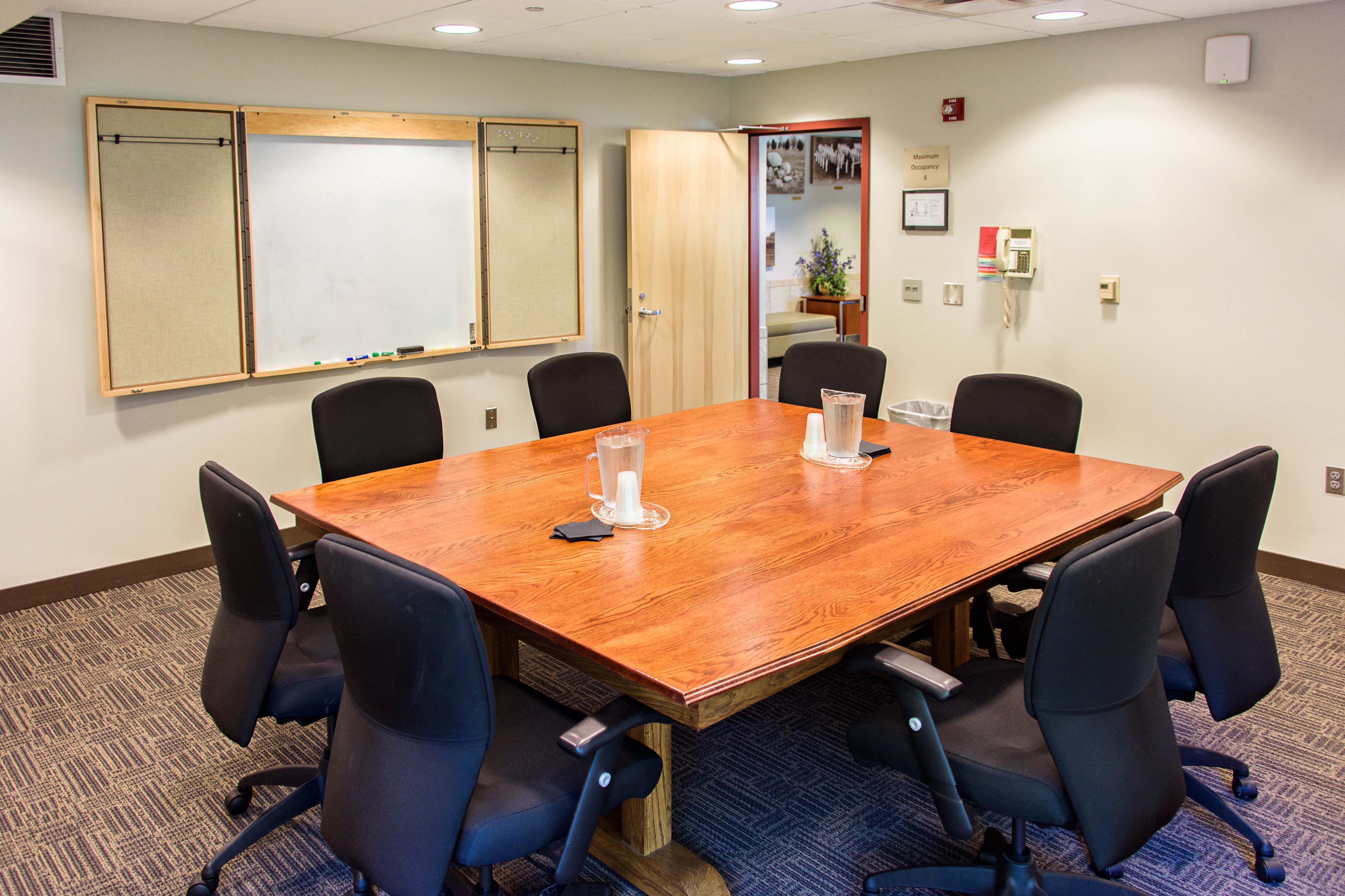 A view of the Bollinger Conference Room that shows its whiteboard, table, and seating
