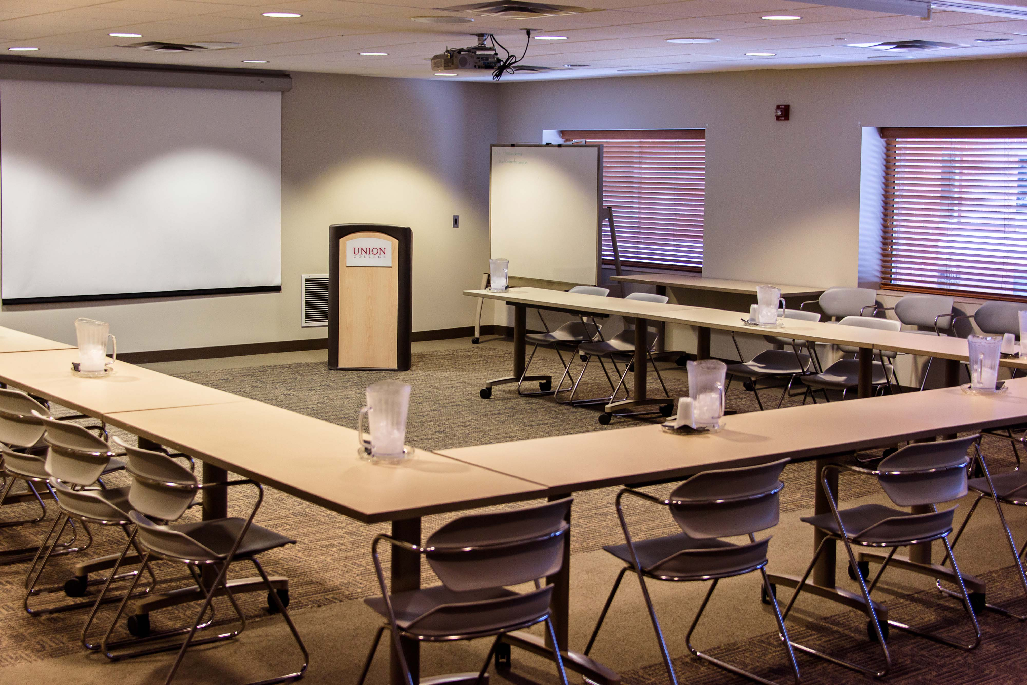 A closer angle showcasing the tables, seating, projector screen, podium, and whiteboard in the Shawnee-Porter Care Conference Room (shown from the back of the room)