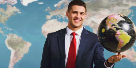 Photo of a student in a suit holding a globe with a map behind him.