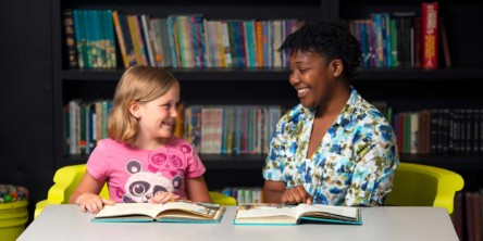 George Stone elementary student and student teacher happily reading books together