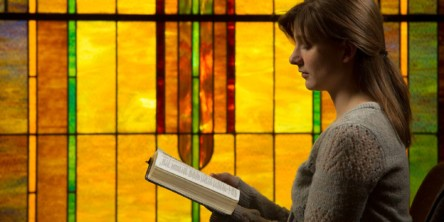 A student reading the Bible by the beautifully lit stained glass in the College View Church